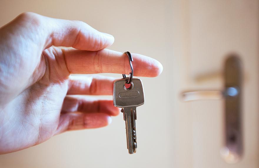 Mann hält einen Wohnungsschlüssel in der Hand.